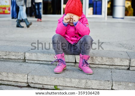 lost girl in the city sitting and crying - stock photo