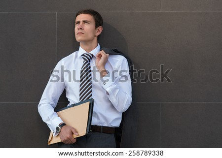 Lost in business thoughts. Thoughtful businessman in formalwear holding documents and looking away while standing against grey wall background
