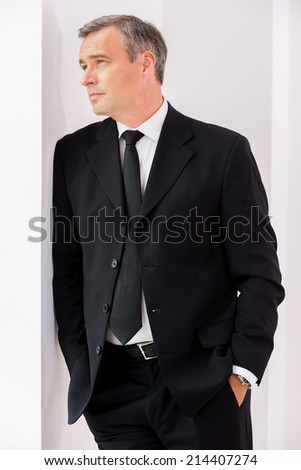 Lost in business thoughts. Thoughtful mature man in formalwear looking away while leaning at the wall - stock photo