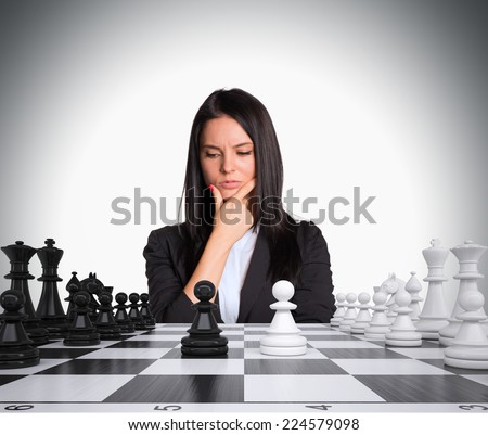 Lost in thought businesswoman looking at chess board with chess. Gray background. Business concept - stock photo