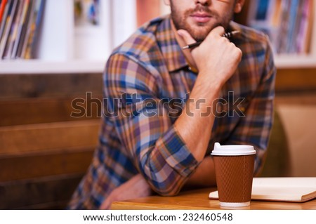Lost in thoughts. Close-up of thoughtful young man holding hand on chin while sitting at the desk in library - stock photo