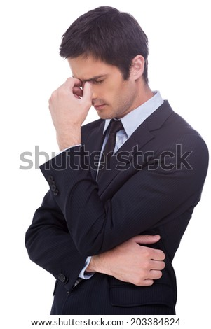 Lost in thoughts. Side view of frustrated young man in white shirt holding hand in hair and keeping eyes closed while standing isolated on white background - stock photo