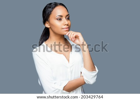 Lost in thoughts. Thoughtful young African woman holding hand on chin and looking away while standing against grey background - stock photo