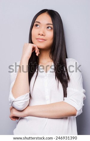 Lost in thoughts. Thoughtful young Asian woman holding hand on chin and looking away while standing grey background - stock photo
