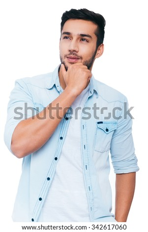 Lost in thoughts. Thoughtful young Indian man holding hand on chin and looking away while standing against white background - stock photo
