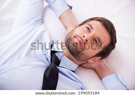Lost in thoughts. Top view of handsome young man in shirt and tie holding hands behind head and smiling while lying in bed