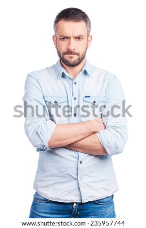 Lost in thoughts. Worried young man in casual wear keeping arms crossed and looking away while standing isolated on white background - stock photo