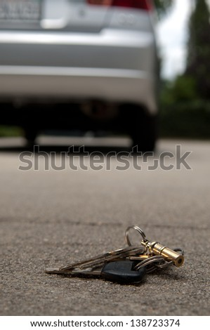 Lost keys dropped on the ground behind a car, forgotten by owner - stock photo