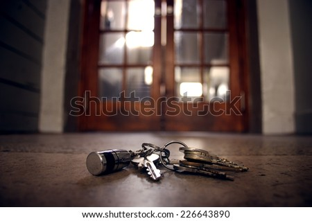 lost keys on the floor in front of the door - stock photo