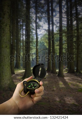 lost man holding compass in middle of forest with many paths to choose from - stock photo
