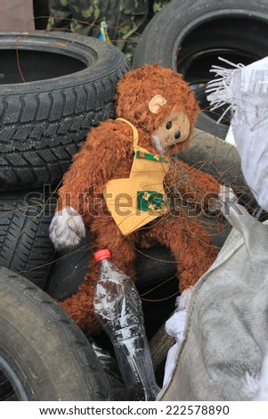Lost old toy monkey among the tires at the Maidan in Kyiv, Ukraine - stock photo