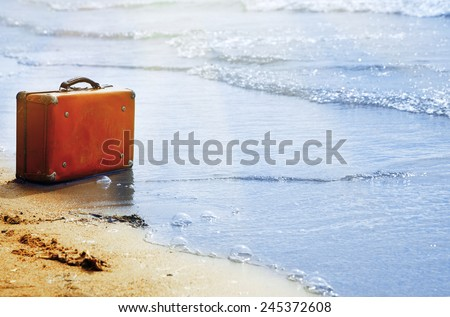 Lost orange handbag on the beach - stock photo