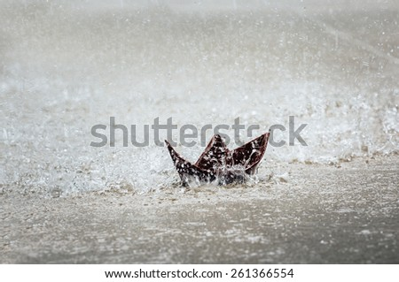 Lost paper boat under the rain. - stock photo