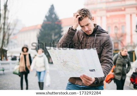 Lost tourist looking at city map on a trip. Looking for directions. - stock photo