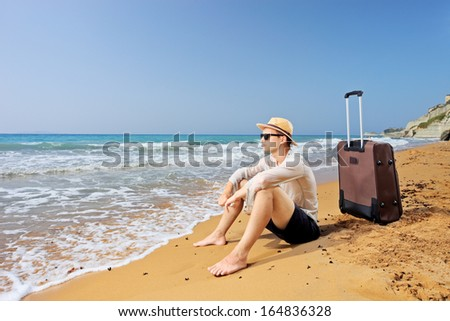Lost tourist on a beach Peroulades at Corfu island, Greece with his luggage