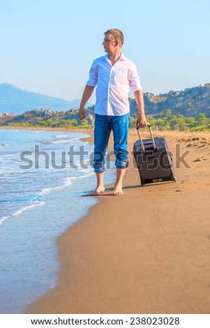 lost traveler with suitcase looking at sea - stock photo