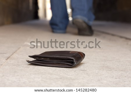 Lost wallet on the street and legs of the walking man concept - stock photo