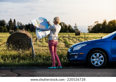 Lost Woman on a Rural Scene Looking at a Map - stock photo