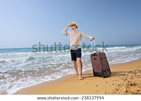 Lost young tourist with his baggage on a sandy beach by the ocean - stock photo