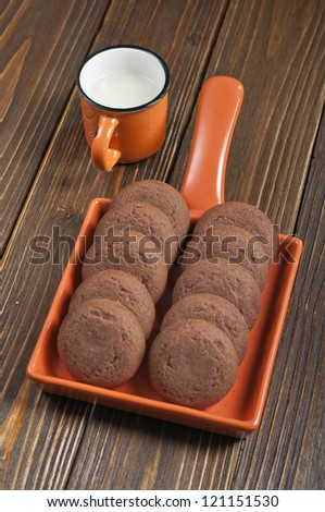 Lot of biscuits in orange ceramic pan and cup of milk on dark wooden background - stock photo