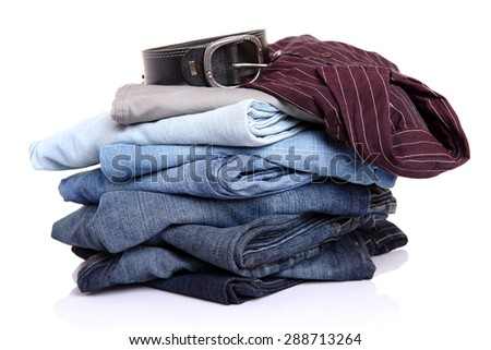 lot of blue jeans with belt and shirt isolated on white - stock photo