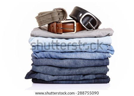 lot of blue jeans with belts isolated on white - stock photo