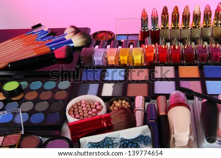 Lot of different cosmetics on pink background - stock photo
