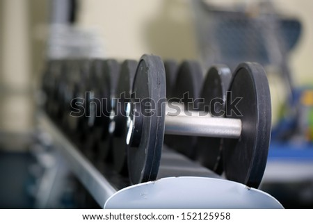 Lot of dumbbells in gym close-up - stock photo