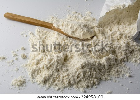 lot of flour on white base, wooden spoon - stock photo