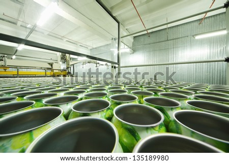 Lot of green aluminum cans for drinks in shop floor at large factory. - stock photo