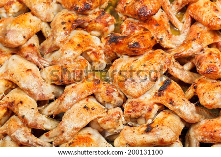 lot of roasted spicy chicken wings on hot tray - stock photo
