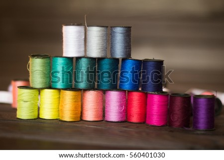 lot of spools of thread of different colors for sewing on wooden background.the photo has a empty space for your text