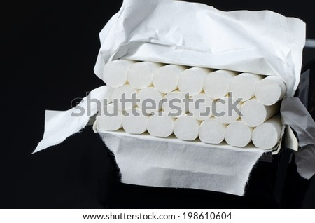 Lot of white cigarettes in paper box isolated on black background. - stock photo
