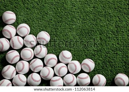 Lots of baseballs on green turf background - stock photo