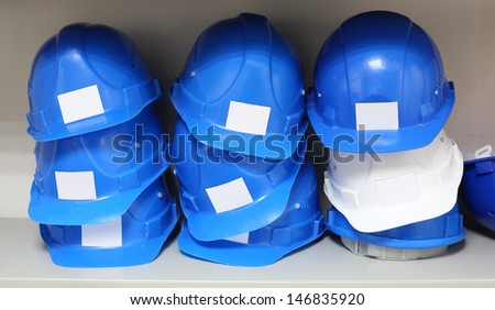 Lots of blue and one white construction helmets are on shelves. - stock photo