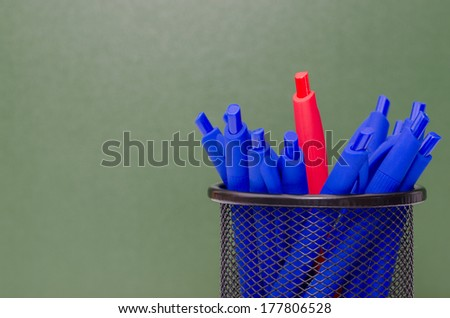 Lots of blue pens and stands in the center a red pen in a nice container to green chalkboard background - stock photo