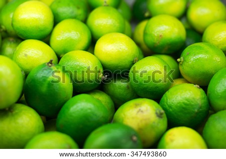 Lots of bright green limes in supermarket. - stock photo