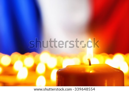 Lots of candles in front of the national colors of France in remembrance of the many victims of terror or to simply symbolize the great French spirit - stock photo