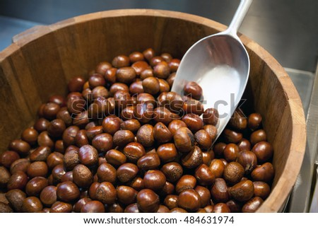 Lots of chestnuts at the market. Pile of nuts in a wood basket with a scoop at supermarket