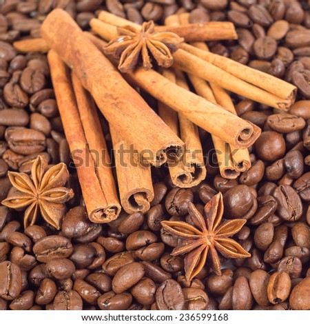 Lots of coffee beans. Three anise stars, lots of sticks of cinnamon. Shallow depth of field. - stock photo