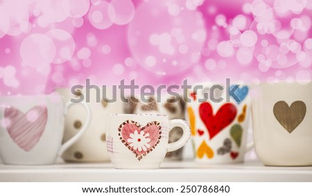 Lots of coffee in different cups with hearts and beautiful pink bokeh.