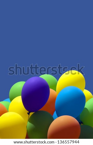 Lots of colorful balloons against a blue sky - stock photo