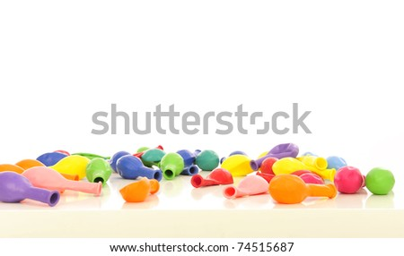 Lots of colorful balloons laying on white background with copyspace - stock photo