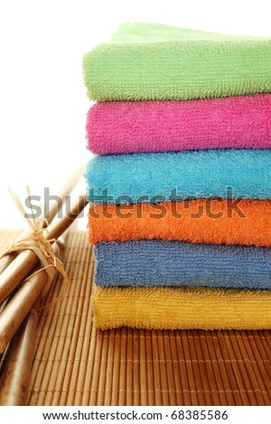 Lots of colorful bath towels stacked on each other. Side by side on a wooden surface lie bamboo sticks. Isolated - stock photo