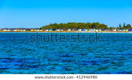 Lots of colorful bathing huts along the shore with a small forest behind. Calm and blue water in front. Falsterbo, Sweden. - stock photo