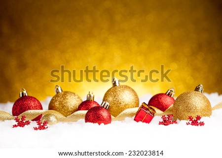 Lots of colorful Christmas Decoration baubles in snow on golden background - stock photo