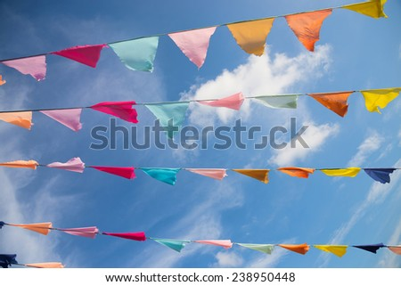 lots of colorful flags against blue sky - stock photo
