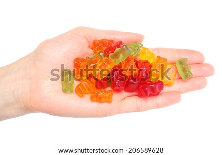Lots of colorful haribo bear candies in hand of woman. Isolated on white background - stock photo
