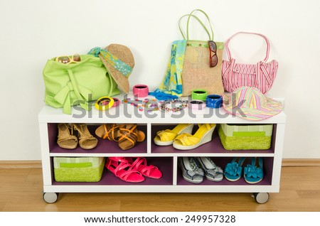 Lots of colorful summer accessories on a shelf. Bags, jewelry, shoes and sandals nicely arranged on a shelf - stock photo