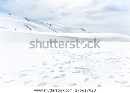 Lots of footprints in the snow covered mountain under cloudy sky - stock photo